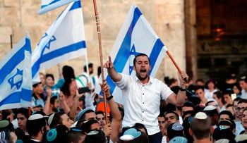 Far right Israeli supporters wave the Israeli flag as they demonstrate on May 24, 2017 in front of Damascus Gate in Jerusalem's Old City to commemorate Jerusalem Day.