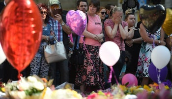 Flowers, messages and candles are pictured alonside a t-shirt from Ariana Grande's Dangerous Woman tour in St Ann's Square in Manchester, northwest England on May 25, 2017, placed in tribute to the victims of the May 22 terror attack at the Manchester Arena.