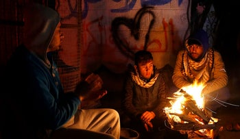 Palestinians sit around a fire outside their home in Gaza City.