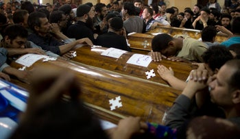 Relatives of Coptic Christians who were killed during a bus attack mourn by their coffins in Minya, Egypt on May 26, 2017.