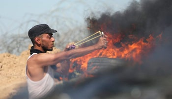 A Palestinian protester using a slingshot to hurl stones toward Israeli troops during clashes near the border between Israel and the Gaza Strip, May 26, 2017.
