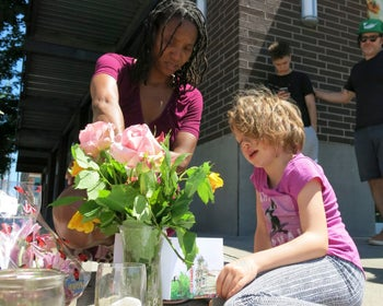 Angel Sauls helps her stepdaughter, Coco Douglas arrange a sign for a memorial for the two bystanders in Portland, on May 27, 2017.