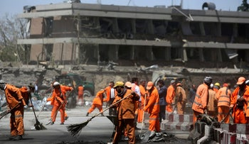 Afghan Municipality workers sweep a road in front of the German Embassy after a suicide attack in Kabul, Afghanistan, May 31, 2017.
