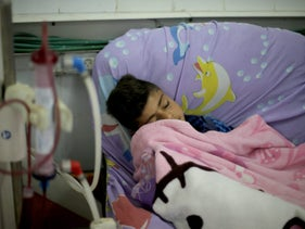 A Palestinian patient sleeps as he undergoes kidney dialysis at Shifa hospital in Gaza City, April 24, 2017.