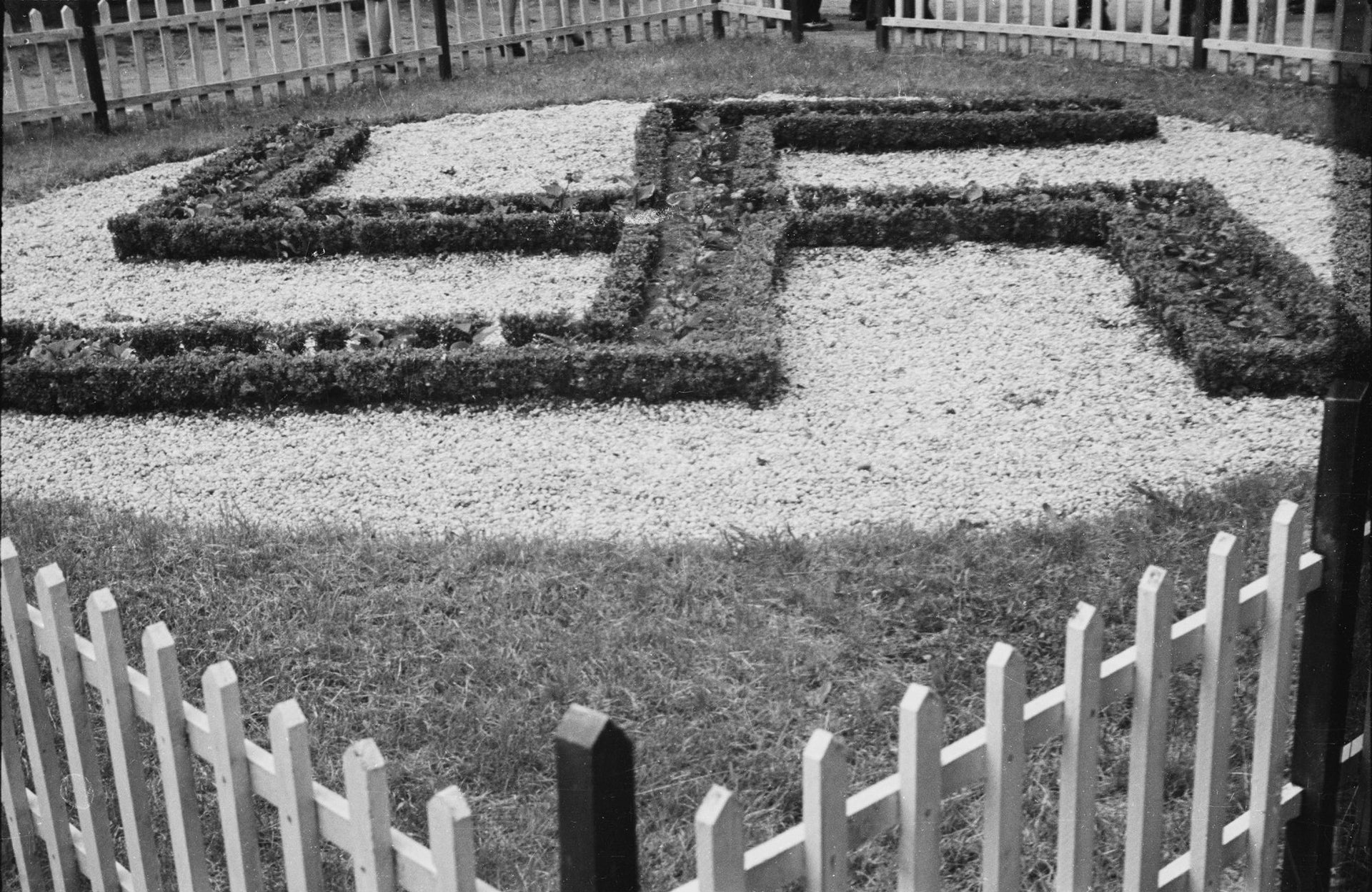 In this May 22, 1938 photo provided by the New York City Municipal Archives, a large swastika is surrounded by a white picket fence at Camp Siegfried in Yaphank, N.Y.