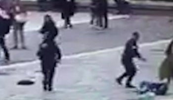 In this image taken from video of CCTV footage, an officer points his gun at an attacker, on the ground, after the Paris attack outside Notre Dame cathedral