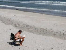 A tourist sits and reads at the seaside on Table Bay beach with a view of Table Mountain, center, in Cape Town, South Africa.