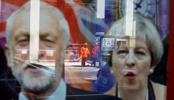 Workers in protective equipment are reflected in the window of a betting shop with a display inviting customers to place bets on tbe result of the general election with images of Britain's Prime Minister Theresa May and opposition Labour Party leader Jeremy Corbyn, in London, June 7, 2017.