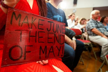An attendee holds a banner with the slogan 'Make June the end of May' in support of Jeremy Corbyn, leader of the U.K. opposition Labour Party, as he delivers a speech on brexit negotiations, as part of the party's general-election campaign in London, U.K., on Thursday, June 1, 2017.