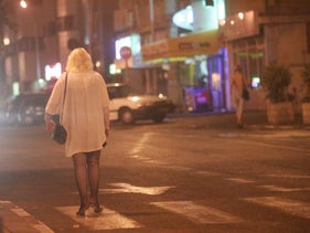 A woman standing on a street corner in a red-light district