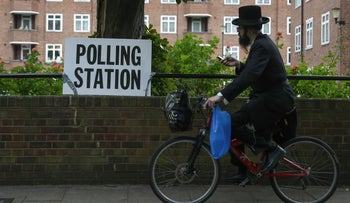 An Ultra-orthodox Jewish man cycles past a polling station sign in northeast London on June 8, 2017.