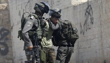 Israeli border police arrest a Palestinian during clashes in the West Bank village of Deir Abu Mash'al near Ramallah, June 17, 2017 a day after an attack in Jerusalem killed a police officer.