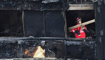 An Urban Search and Rescue officer from London Fire Brigade inside the Grenfell Tower in west London after a fire engulfed the 24-storey building on Wednesday morning, Saturday, June 17, 2017. Public fury over the London high-rise fire is mounting as exhausted London firefighters continue their grim search Saturday for victims of the inferno that killed at least 30 people. (David Mirzoeff/PA via AP)