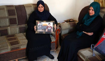 The mother of Osama Ata, one of the assailants in the Jerusalem attack, holds up his picture at their home in the village of Deir Abu Mashal near the West Bank city of Ramallah, June 17, 2017.