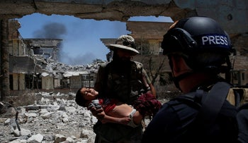 An Iraqi soldier hands over a dehydrated child he rescued at the front line of the battle for the ISIS-held city of Mosul, Iraq, June 13, 2017.