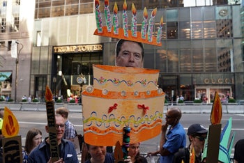Protesters display placards during a demonstration against US President Donald Trump to mark his Birthday, in New York on June 14, 2017