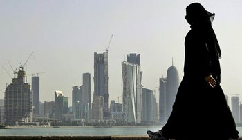 In this May 14, 2010 file photo, a Qatari woman walks in front of the city skyline in Doha, Qatar