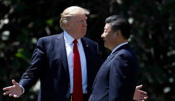 Donald Trump and Chinese President Xi Jinping sit as they pose for photographers before a meeting at Mar-a-Lago in Palm Beach, Fla.