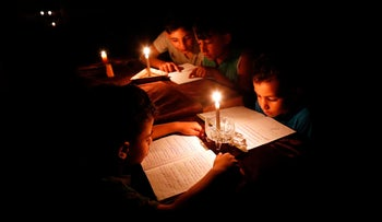 Palestinian children read books by candlelight due to electricity shortages in Gaza City, Gaza, June 13, 2017.