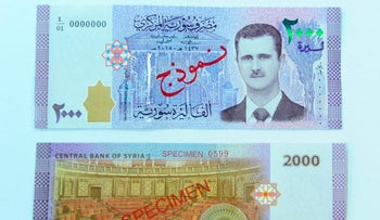 A portrait of Syria's President Bashar al-Assad is seen printed on the new Syrian 2,000-pound banknote that went into circulation on Sunday, in this handout picture provided by SANA on July 2, 2017, Syria.