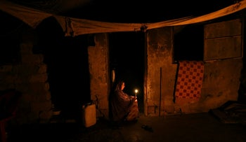 A Palestinian woman lights a candle inside her house during power cut in the southern Gaza Strip June 11, 2017.