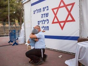 "A father embraces his son at the protest ""field hospital"" set up by parents of children from the Hadassah cancer ward in Jerusalem's Sacher Park, June 4, 2017."
