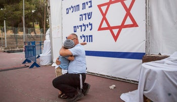 """A father embraces his son at the protest """"field hospital"""" set up by parents of children from the Hadassah cancer ward in Jerusalem's Sacher Park, June 4, 2017."""