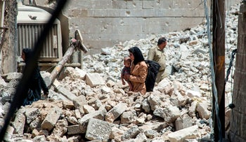An Iraqi woman carries a child as she walks through the rubble in the Old City of Mosul on July 2, 2017, during the offensive to retake the city from Islamic State (IS) group fighters.