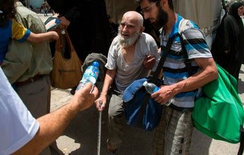 A bottle of water is handed over to an Iraqi man who fled the fighting in the Old City of Mosul, in the city's western industrial district on July 2, 2017, as government forces continue the offensive to retake the city from Islamic State (IS) group fighters.