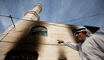 A Palestinian inspects a mosque damaged in a suspected Jewish right-wing 'price tag' attack in the West Bank village of Mughayer, north of Ramallah. Nov. 12, 2014