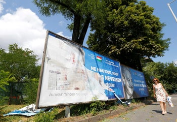 """The Hungarian government poster portraying financier George Soros and saying """"Let's not let George Soros have the last laugh"""" is seen in the street in Budapest, July 11, 2017."""