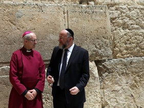 Chief British Rabbi Ephraim Mirvis, in dark suit and tie, meets with Archbishop of Canterbury Justin Welby, in red, at the Western Wall, May 2017.