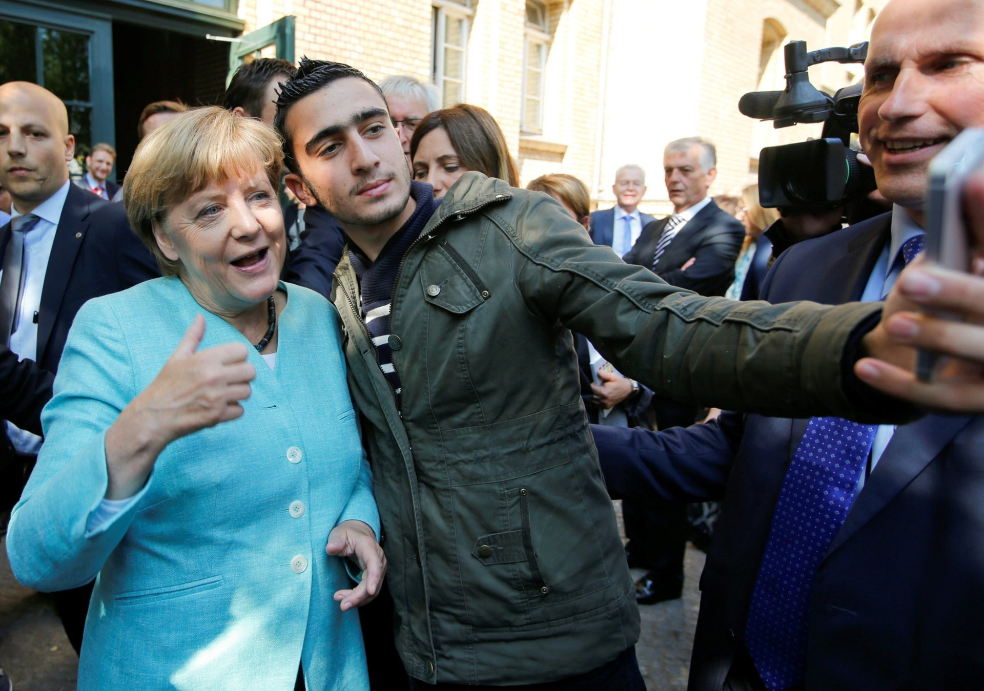 Syrian refugee Anas Modaman takes a selfie with German Chancellor Angela Merkel.