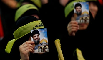 Hezbollah supporters cover their faces with portraits of leader Hassan Nasrallah in Beirut, Lebanon, on June 23, 2017.