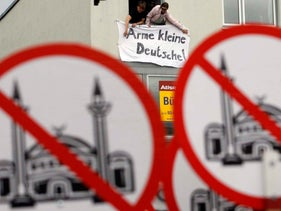 Protesters display a banner reading 'Poor little Germans,' in front of a right-wing demonstration against the construction of a mosque in Cologne, Germany.