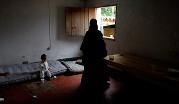A woman and a child of a Jewish community are seen at their home as they prepare to leave the village of San Juan La Laguna August 28, 2014.