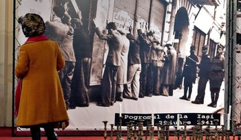 An elderly woman looks at a photograph of Romanian Jews being rounded up by authorities in Iasi, Romania, in 1941, at a Holocaust memorial exhibition in Bucharest, Romania, January 25, 2004.