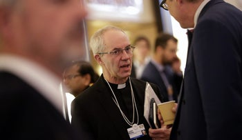 Justin Welby, Archbishop of Canterbury speaks to an attendee between sessions during the World Economic Forum (WEF) in Davos, Switzerland, on Jan. 22, 2016.