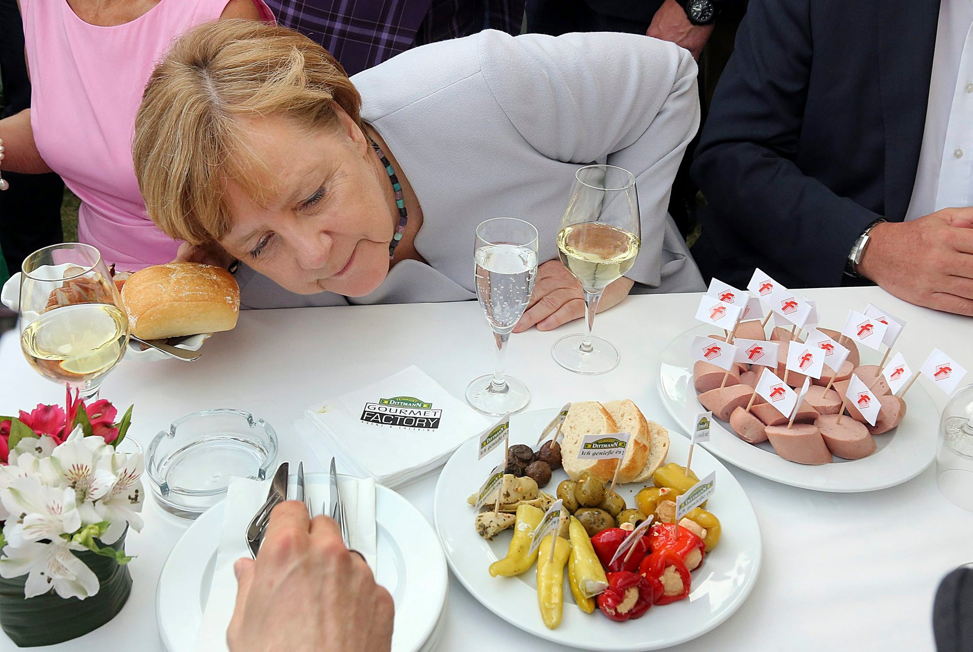 German Chancellor Angela Merkel looks at the culinary delicacies on offer during the Hesse Festival in the Hessian State Representation in Berlin, Germany, Wednesday, June 21, 2017.