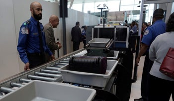 Baggage and a laptop are scanned at Terminal 4 of JFK airport in New York City on May 17, 2017.