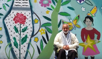 The council head of the West Bank town of Aqaba, Sami Sadeq, sits in front of a mural depicting pre-1948 Palestine