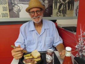 Alan Gross with some of his favorite things — a pastrami sandwich and a Cuban cigar — at Loeb's Deli in Washington, D.C., July 12, 2017.