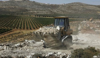 A bulldozer clears the land for the new settlement, Amichai, between Ramallah and Nablus in the Israeli-occupied West Bank, on June 20, 2017.