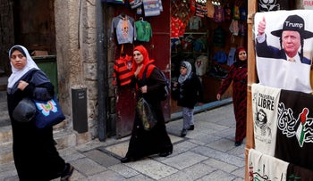 Palestinian women walk past a stall displaying T-shirts in Jerusalem's Old City, November 9, 2016.
