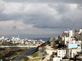 The Israeli barrier running along the East Jerusalem refugee camp of Shoafat (L) as the East Jerusalem neighborhood of Isawiyah is seen on the right, February 15, 2017