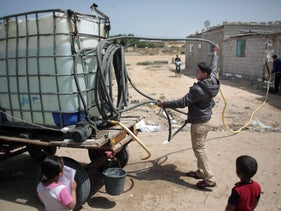 A Palestinian man sells drinking water in Khan Younis refugee camp in the Gaza Strip, April 16, 2016.