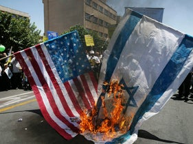 Iranian protesters burn Israeli and American flags in a rally marking al-Quds Day in Tehran, June 23, 2017.