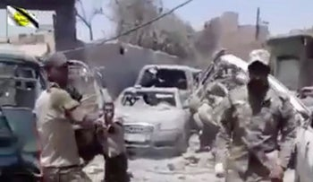 This photo made from undated video posted online shows a man in an Iraqi Army uniform moments before shooting an unarmed man believed to be an ISIS fighter in Mosul, Iraq