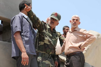 Hamas chief in Gaza Yahya Sinwar (R) visits the border with Egypt, in Rafah in southern Gaza Strip on July 6, 2017.