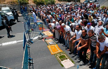 Muslim worshipers pray on a street outside the Lion Gate as Israeli police blocks the access to Al-Aqsa Mosque following a shooting attack on July 14, 2017.